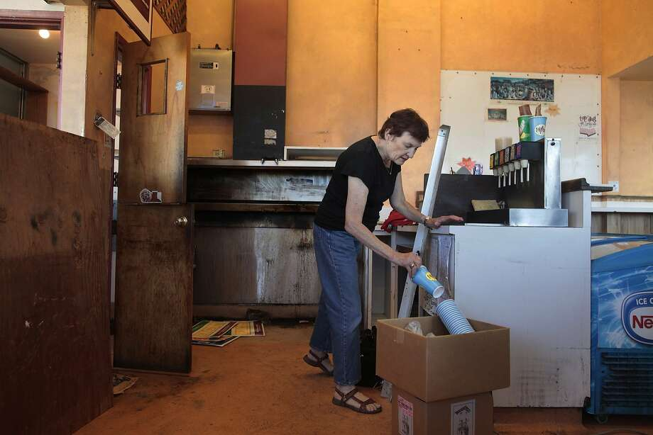 Rinie Riemann packs up Top Dog, which is slated to close along with CVS in Oakland. Photo: James Tensuan, The Chronicle