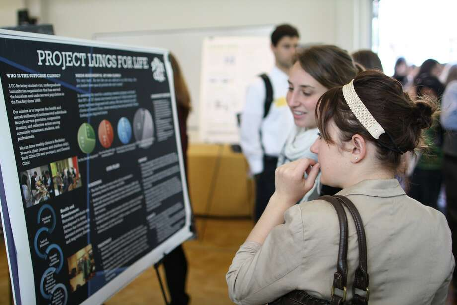 Brenna Alexander, left, and Allie Wallace read a poster for their team's Suitcase Clinic entry in the Big Ideas@Berkeley student idea competition. Photo: Alexander