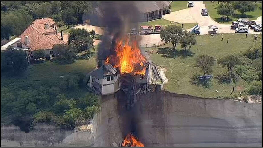 Crews have burned a luxury home that was dangling from a crumbling cliff overlooking Texas' Lake Whitney. Photo: KTVT-TV