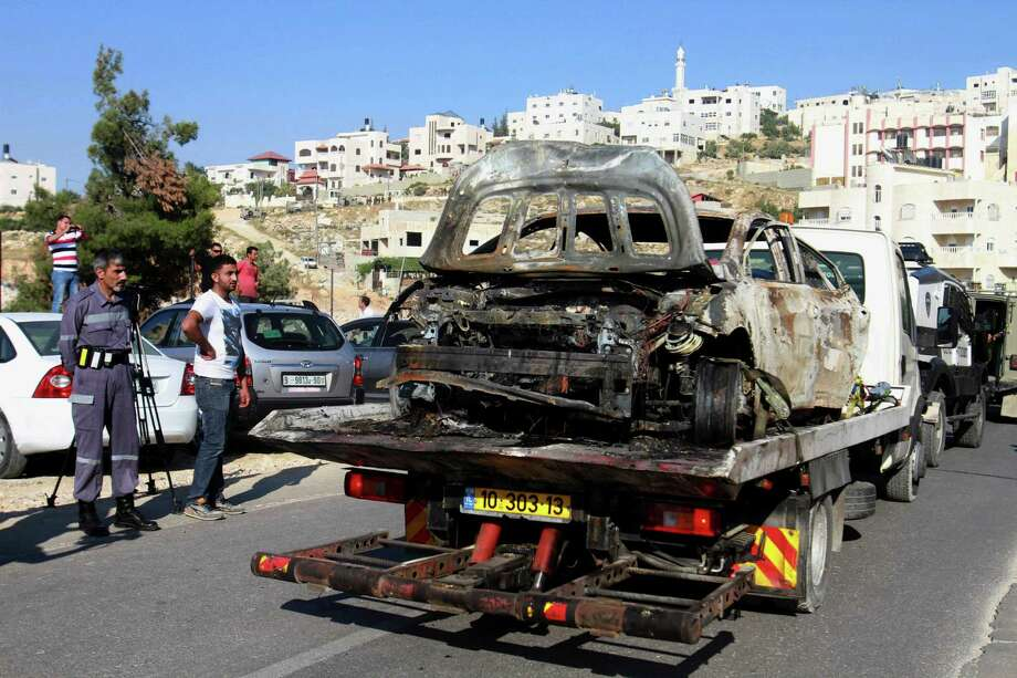 A burnt car reportedly connected to the disappearance of three teenagers is taken away near the West Bank city of Hebron on Friday.  Photo: Nasser Shiyoukhi, STF / AP