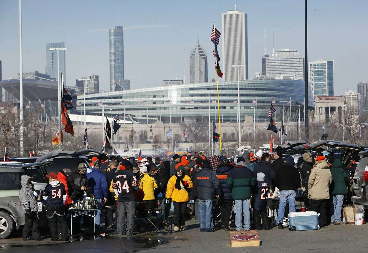 FILE - In this Jan. 23, 2011 file photo, football fans tailgate in a parking lot south of Soldier Field, in the background, before a Chicago Bears game in Chicago. Chicago Mayor Rahm Emanuel is trying to persuade