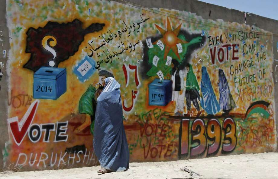 An Afghan woman walks past a mural to support voting in Kandahar, south of Kabul, Afghanistan, Friday, June 13, 2014. With fears of violence high, Afghanistan braced for a final election on Saturday to choose a new president to replace the only leader the nation has known since the Taliban were ousted and guide the transition to a country that will have to wean itself off near-total dependence on international aid after foreign combat troops withdraw at the end of this year. (AP Photo/Allauddin Khan) Photo: Allauddin Khan, STR / AP