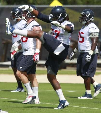 Justin Tuggle stretches. Photo: Melissa Phillip, Houston Chronicle