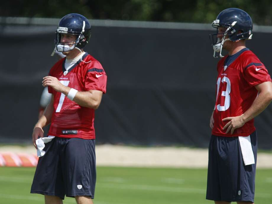 Case Keenum (7) and T.J. Yates (13) talk about a drill. Photo: Melissa Phillip, Houston Chronicle