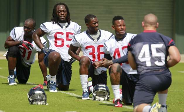 Jason Ankrah (65), Andre Hal (38) and others stretch. Photo: Melissa Phillip, Houston Chronicle
