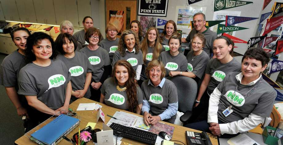 "Students and staff at New Milford High School have created the ""We Care"" initiative to promote drug-free living. Rebecca Nusser, 17, seated left, designed the t-shirt and Denise Duggan, 55, seated right, chairman of the Department of Health and Physical Education spear-headed the effort. Some of the schools staff of secretaries, teachers and nurses pose with them for a photo Friday, June 13, 2014. Photo: Carol Kaliff / The News-Times"