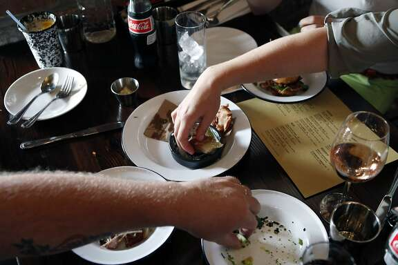 Members of the Sieben family reach for appetizers with their hands while eating at the Dock restaurant in Oakland, CA, Tuesday June 10, 2014.