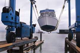 Jose Vargas uses a travel lift to lower a boat into the harbor at the San Francisco Boat Works repair yard on Thursday, June 12, 2014 in San Francisco, Calif.