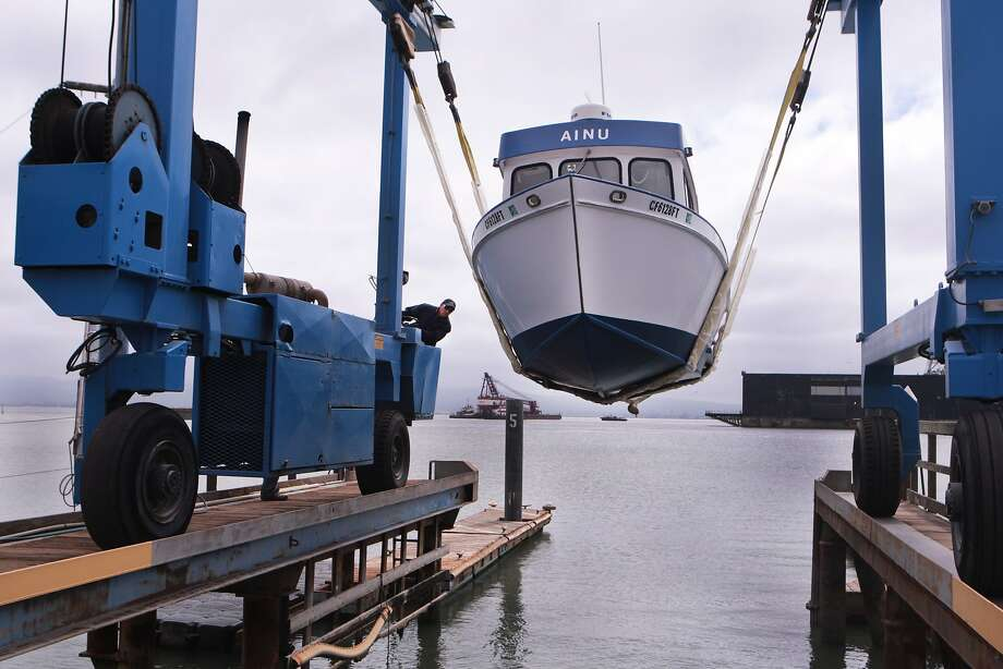 Jose Vargas uses a travel lift to lower a boat into the harbor at the San Francisco Boatworks repair yard. Photo: Kevin N. Hume, The Chronicle