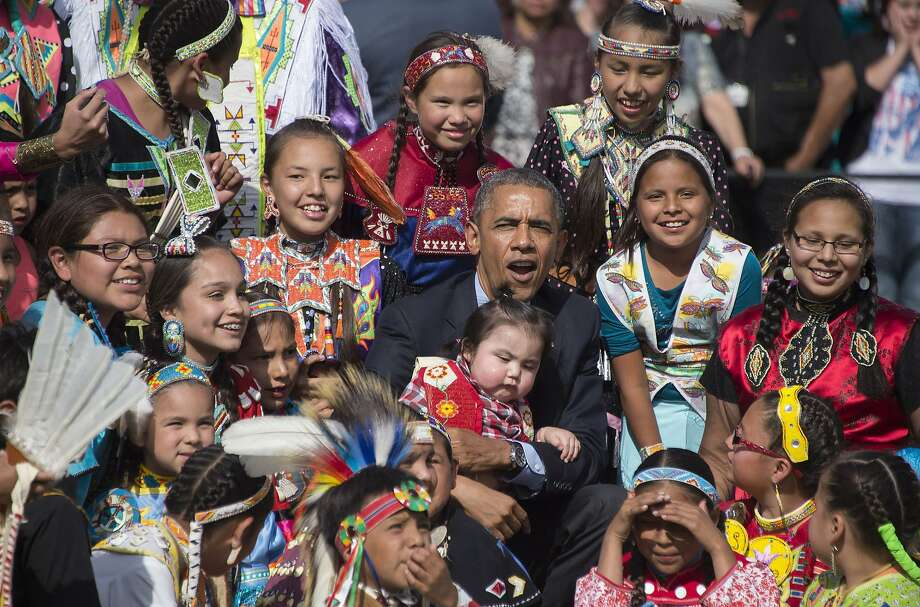 US President Barack Obama (C) holds a child as he poses with Native American performers during the Cannon Ball Flag Day Celebration in Cannon Ball, North Dakota, June 13, 2014.       AFP PHOTO / Jim WATSONJIM WATSON/AFP/Getty Images Photo: Jim Watson, AFP/Getty Images