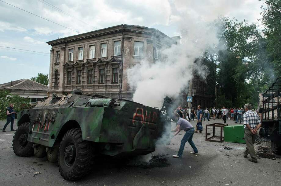 Local citizens gather around a burning military vehicle at a site of a battle between Ukrainian troops and pro-Russian fighters in Mariupol, eastern Ukraine, Friday, June 13, 2014. Ukraine's interior minister says that government troops have attacked pro-Russian separatists in the southern port of Mariupol. Arsen Avakov said Friday that four government troops were wounded as forces retook buildings occupied by the rebels in the center of the town. (AP Photo/Evgeniy Maloletka) Photo: Evgeniy Maloletka, STR / AP