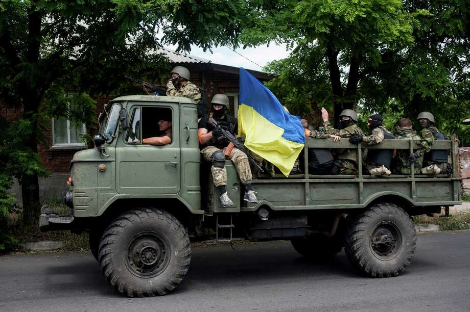 Ukrainian troops with a Ukrainian national flag sit atop a vehicle while they leave a scene of a battle in Mariupol, eastern Ukraine, Friday, June 13, 2014. Ukraine's interior minister says that government troops have attacked pro-Russian separatists in the southern port of Mariupol. Arsen Avakov said Friday that four government troops were wounded as forces retook buildings occupied by the rebels in the center of the town. (AP Photo/Evgeniy Maloletka) Photo: Evgeniy Maloletka, STR / AP