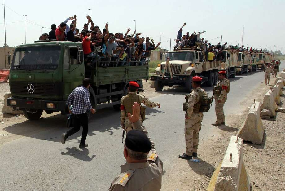 Truck-borne Iraqis at a recruiting center in Baghdad salute their countrymen after volunteering to fight against the militants advancing toward the capital. Photo: ALI AL-SAADI, Staff / AFP