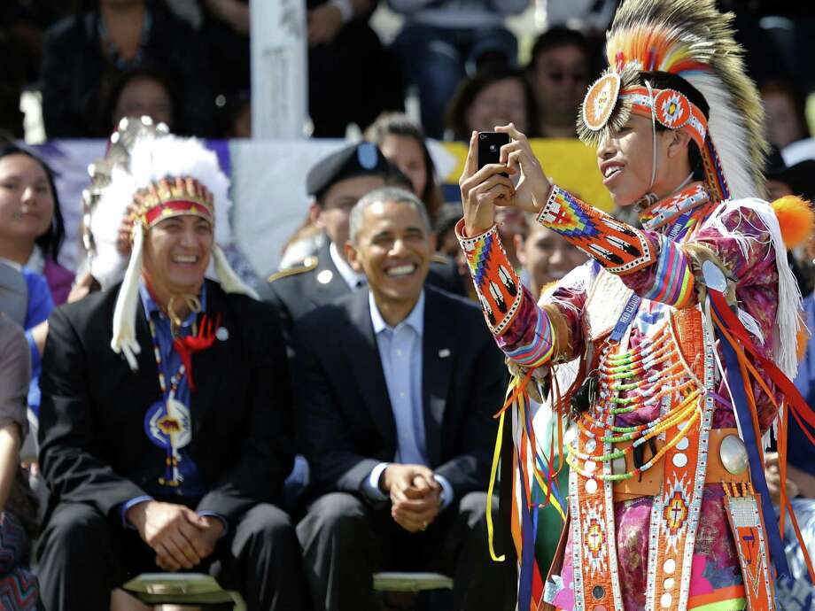 A Native American dancer creates a selfie with President Barack Obama and Chairman if the Standing Rock Sioux Tribe David Archambault, left, on the Standing Rock Indian Reservation Friday, June 13, 2014, photo in Cannon Ball, N.D. President Obama is making his first presidential visit to Indian Country for a look at two sides of Native American life, a celebration of colorful cultural traditions on the powwow grounds and a view of the often bleak modern-day conditions on tribal lands. (AP Photo/Charles Rex Arbogast) Photo: Charles Rex Arbogast, STF / AP