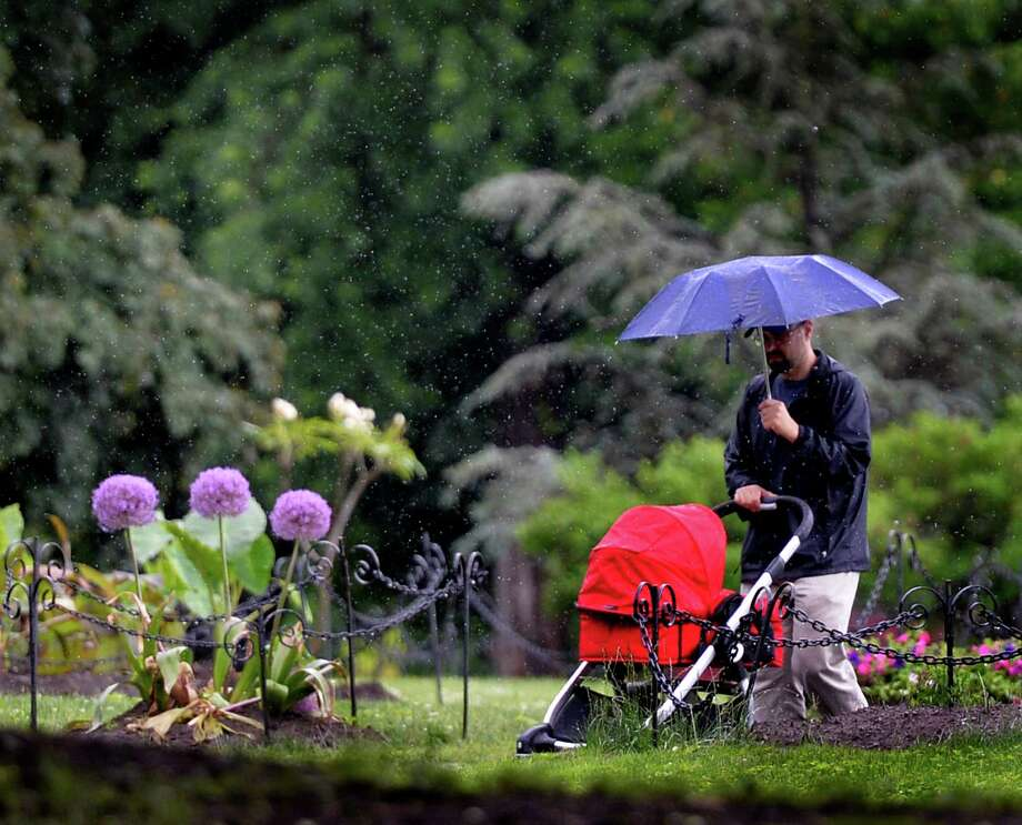 James Walker pushes his daughter, Olana, in her carriage through Washington Park, Friday afternoon, June 13, 2014, in Albany, N.Y.   (Skip Dickstein / Times Union) Photo: SKIP DICKSTEIN