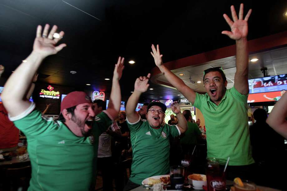 Tony Landero, Richard Martinez, and Gustavo Adolfo cheer as Mexico scores a goal in the second half of the World Cup's Mexico vs Cameroon game during a Dynamo viewing party at Pluckers Wing Bar on June 13, 2014, in Houston, Tx. Photo: Mayra Beltran, Houston Chronicle / © 2014 Houston Chronicle