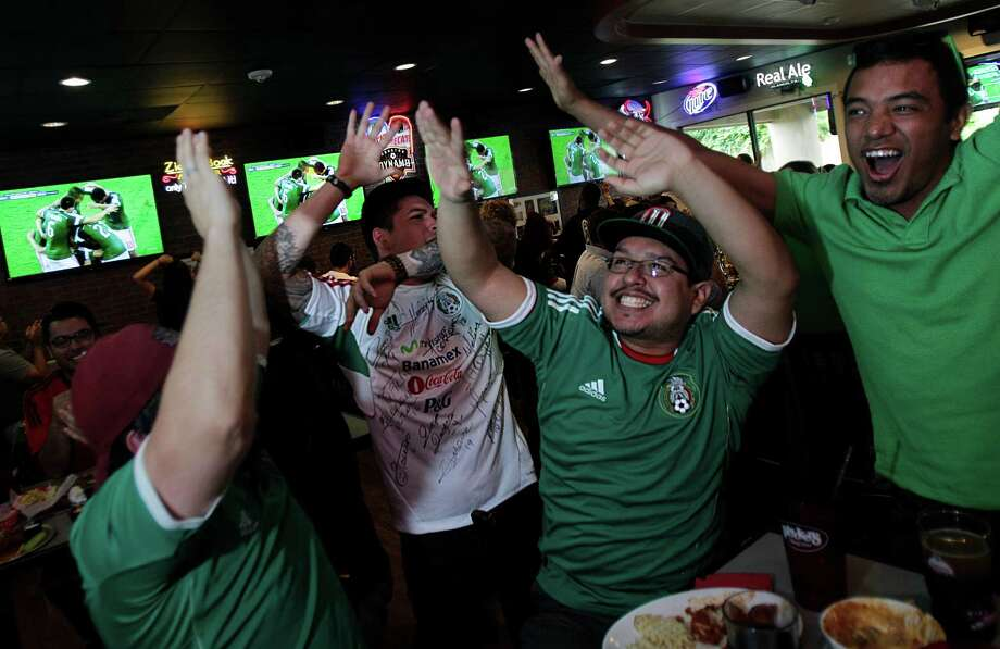 Tony Landero, Oscar Servin, Richard Martinez, and Gustavo Adolfo cheer as Mexico scores a goal in the second half of the World Cup's Mexico vs Cameroon game during a Dynamo viewing party at Pluckers Wing Bar on June 13, 2014, in Houston, Tx. Photo: Mayra Beltran, Houston Chronicle / © 2014 Houston Chronicle