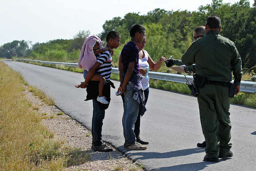 U.S. Border Patrol agents question a group of adult and minor immigrants near Anzalduas Park, southwest of McAllen, Texas, Wednesday, June 11, 2014. A wave of Central American adults with children and unaccompanied minors has overwhelmed U.S. Immigration and Customs detention centers. Immigration officials release some of them on their own recognizance after undergoing processing. Photo: Jerry Lara, San Antonio Express-News / ©2014 San Antonio Express-News