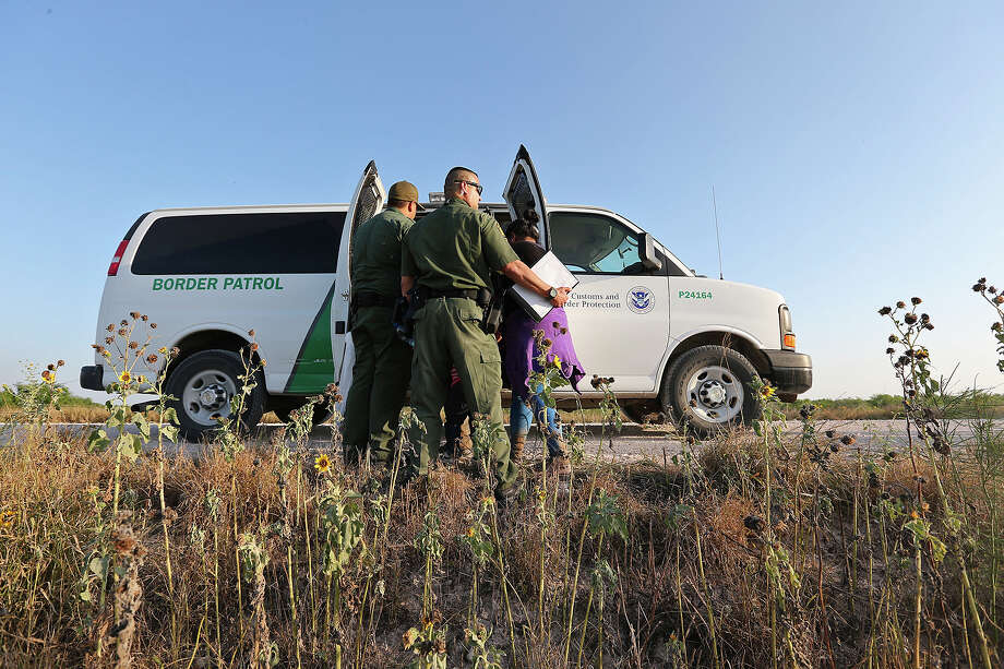 To avoid media attention, immigrant adults and children are hustled into a transportation van by U.S. Border Patrol agents near Anzalduas Park, southwest of McAllen. Photo: Jerry Lara, San Antonio Express-News / ©2014 San Antonio Express-News
