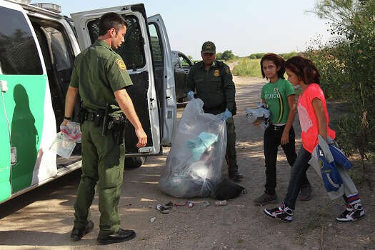 U.S. Border Patrol agents prepare to transport a couple of minor female immigrants in Hidalgo, County southwest of McAllen, Texas, Wednesday, June 11, 2014. A wave of Central American adults with children and unaccompanied minors has overwhelmed U.S. Immigration and Customs detention centers. Immigration officials release some of them on their own recognizance after undergoing processing. Photo: Jerry Lara, San Antonio Express-News / ©2014 San Antonio Express-News