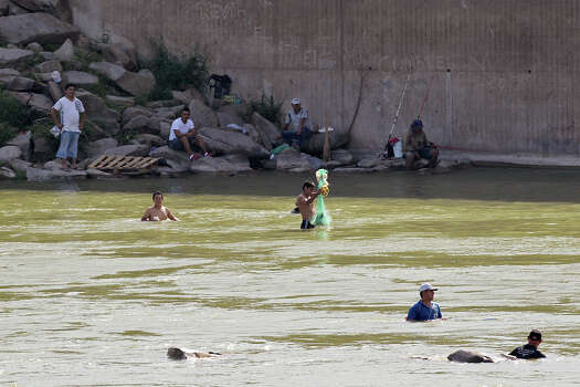 Men from the Mexican side of the Rio Grande fish the river by Anzalduas Dam, southwest of McAllen, Texas, Wednesday, June 11, 2014. According to law enforcement officials onsite, some of them act as lookouts for smuggling rings. A wave of Central American adults with children and unaccompanied minors has overwhelmed U.S. Immigration and Customs detention centers. Immigration officials release some of them on their own recognizance after undergoing processing. Photo: Jerry Lara, San Antonio Express-News / ©2014 San Antonio Express-News
