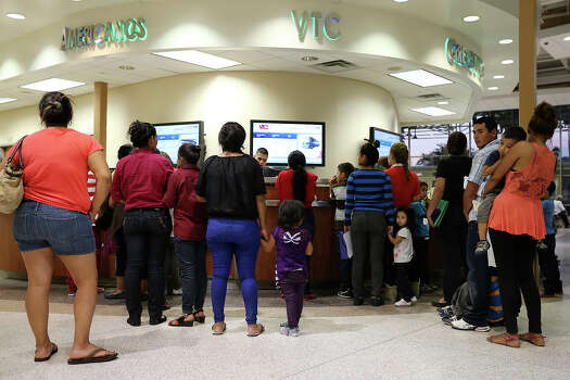 Recently released immigrants from Central American line up to receive bus tickets at the terminal in McAllen, Texas, Wednesday, June 11, 2014. A wave of Central American adults with children and unaccompanied minors has overwhelmed U.S. Immigration and Customs detention centers. Immigration officials release some of them on their own recognizance after undergoing processing. Relatives or friends of the immigrants provide the fund for the purchase of the tickets. Photo: Jerry Lara, San Antonio Express-News / ©2014 San Antonio Express-News