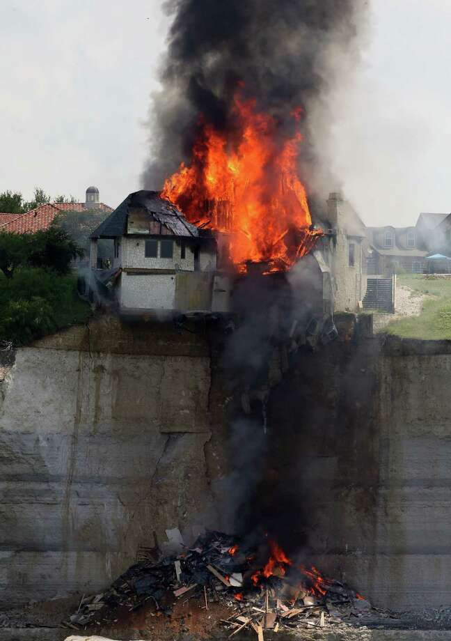 A $700,000 vacation home perched on a crumbling cliff overlooking Lake Whitney is engulfed by fire as demolition crews deliberately burned the structure to the ground rather than wait for it to crumble into the water as the land faltered around it, Friday, June 13, 2014, near Whitney, Texas. The house was condemned earlier after a fracture appeared in the bluff on which it was built. (AP Photo/Waco Tribune Herald, Rod Aydelotte) Photo: Rod Aydelotte, Associated Press / Waco Tribune Herald