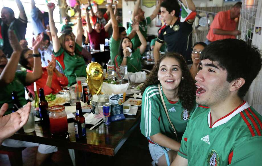Jason Villarreal and Kristen Coatney celebrate at 210 Ceviche Seafood Cocina, packed full of Mexico soccer fans, after Mexico's winning goal in a World Cup match against Cameroon. Photo: Bob Owen / San Antonio Express-News / © 2012 San Antonio Express-News