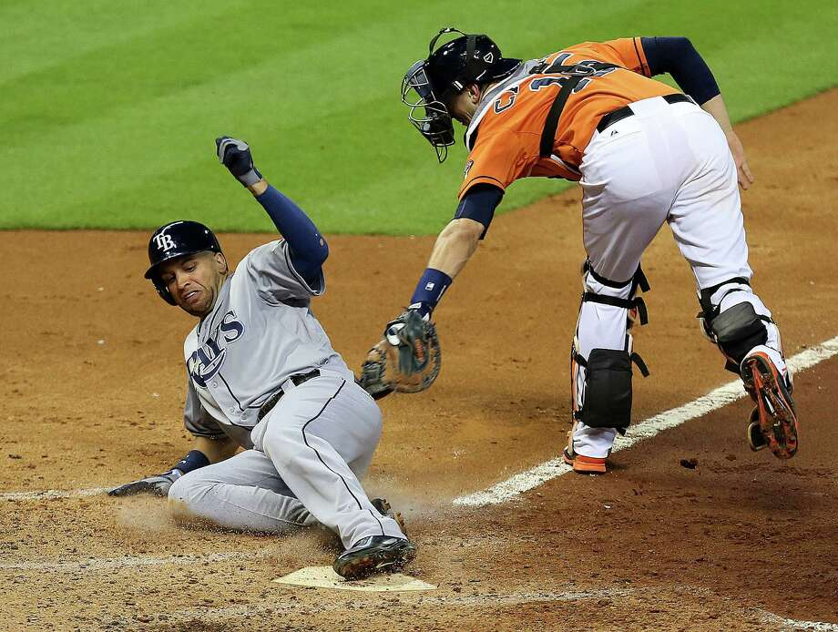 Tampa Bay Rays first baseman James Loney, left, beats Astros catcher Jason Castro to home plate to score a run during the fifth inning. Tampa Bay grabbed a 6-1 win over the Astros on Friday night. Photo: James Nielsen, Staff / © 2014  Houston Chronicle