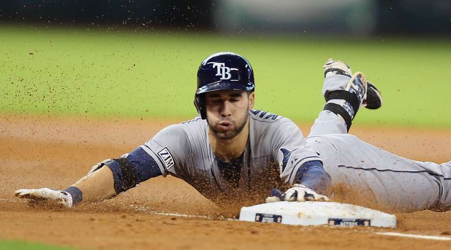 Rays right fielder Kevin Kiermaier slides into third base after hitting a triple during the third inning. Photo: James Nielsen, Houston Chronicle