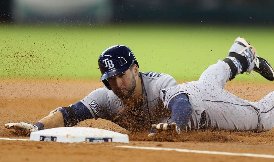 Rays right fielder Kevin Kiermaier slides into third base after hitting a triple during the third inning.