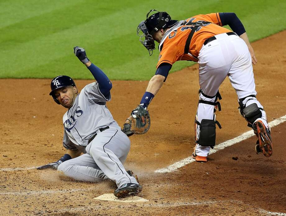 Rays first baseman James Loney, left, beats catcher Jason Castro to home plate to score a run during the fifth inning. Photo: James Nielsen, Houston Chronicle