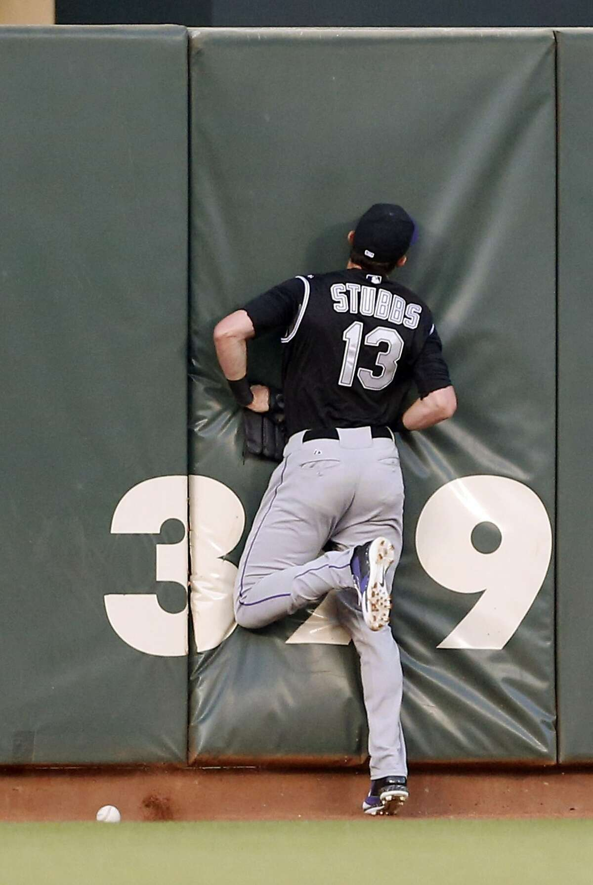 Colorado Rockies center fielder Drew Stubbs collides with the wall and is unable to catch a ball hit by San Francisco Giants' Angel Pagan during the third inning of a baseball game in San Francisco, Friday, June 13, 2014. (AP Photo/Beck Diefenbach)