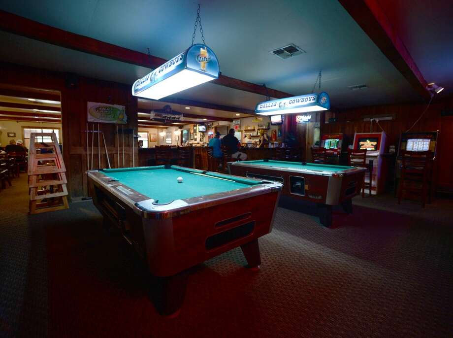 A pair of pool tables and some electronic games are seen near the bar area of the Pine Tree Lodge on Friday afternoon. Pine Tree Lodge on Taylor Bayou is the Cat5 Bar of the Week for June 5, 2014. Photo taken Friday 5/30/14 Jake Daniels/@JakeD_in_SETX