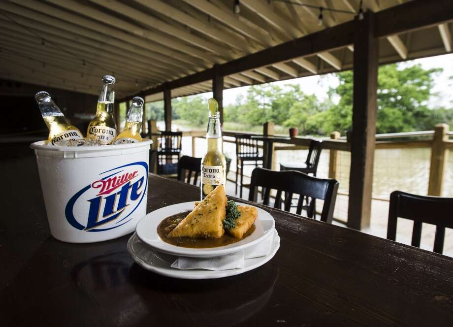 Pictured is a bucket of beer and a plate of shrimp and grits, a new addition to the menu at the Pine Tree Lodge. Pine Tree Lodge on Taylor Bayou is the Cat5 Bar of the Week for June 5, 2014. Photo taken Friday 5/30/14 Jake Daniels/@JakeD_in_SETX