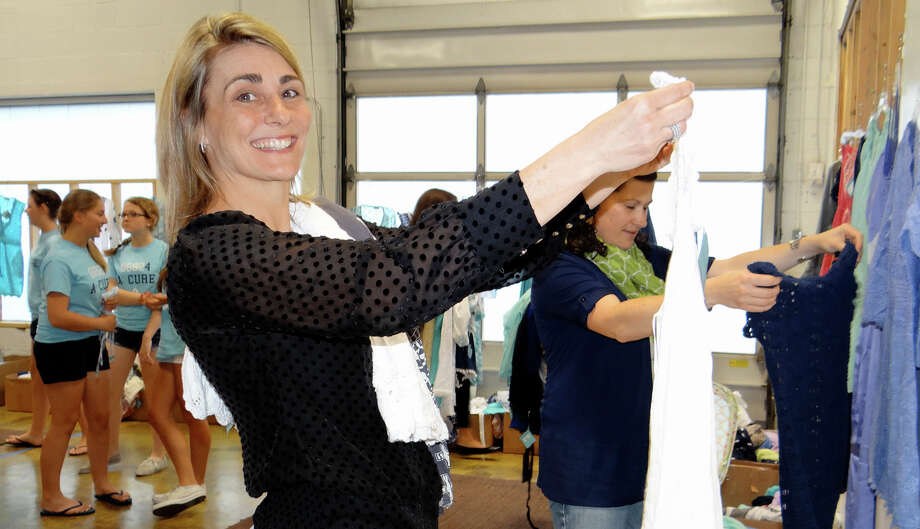 Johanna Salvino looks over the suits on sale at the Letarte Swimwear's charity fundraiser Friday in advance of its annual warehouse sale. Photo: Mike Lauterborn / Fairfield Citizen