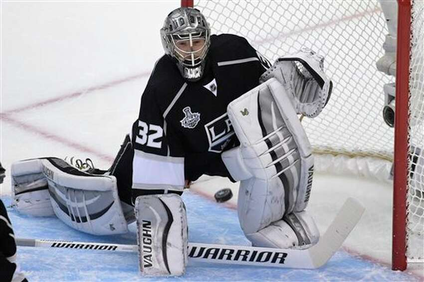 Los Angeles Kings goalie JonathanQuick carries the Stanley Cup after the Kings beat the New York Rangers in Game 5 of the NHL Stanley Cup Final series Friday, June 13, 2014, in Los Angeles. The Kings won, 3-2. (AP Photo/Mark J. Terrill)