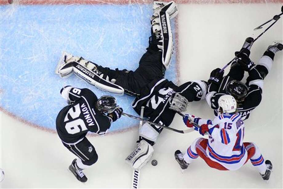 Los Angeles Kings goalie Jonathan Quick makes a save as New York Rangers right wing Derek Dorsett (15) fights  for the puck during the second period of Game 5 of the NHL Stanley Cup  Final series Friday, June 13, 2014, in Los Angeles. (AP Photo/Mark J.  Terrill)