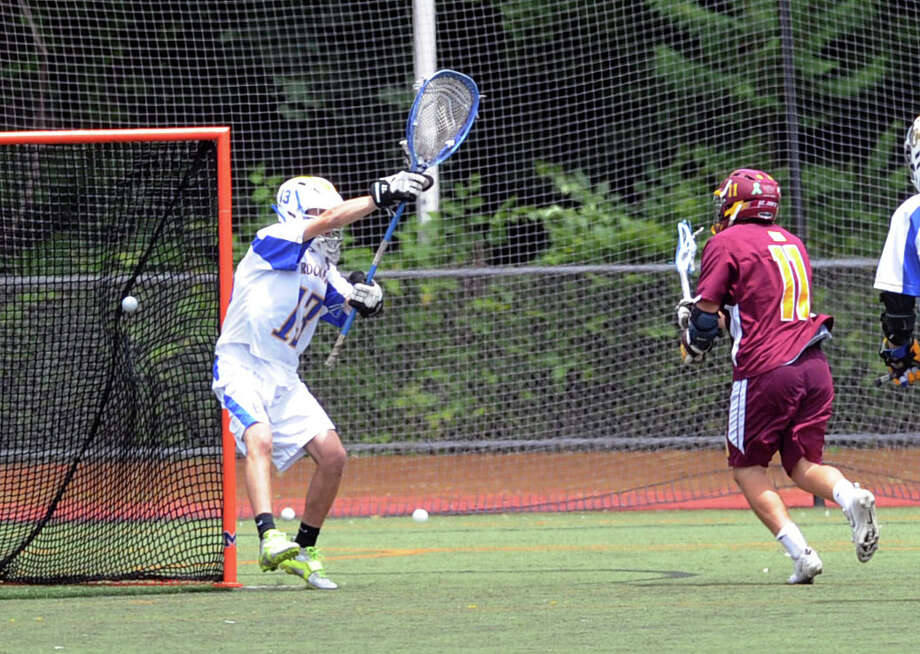 At right, Ryan Corcoran (#11) of St. Joe's gets his shot past Brookfield goalie Dan Dixon for a goal during the Class S state championship lacrosse match between Brookfield High School and St. Joseph High School at Brien McMahon High School in Norwalk, Saturday, June 14, 2014. Photo: Bob Luckey / Greenwich Time