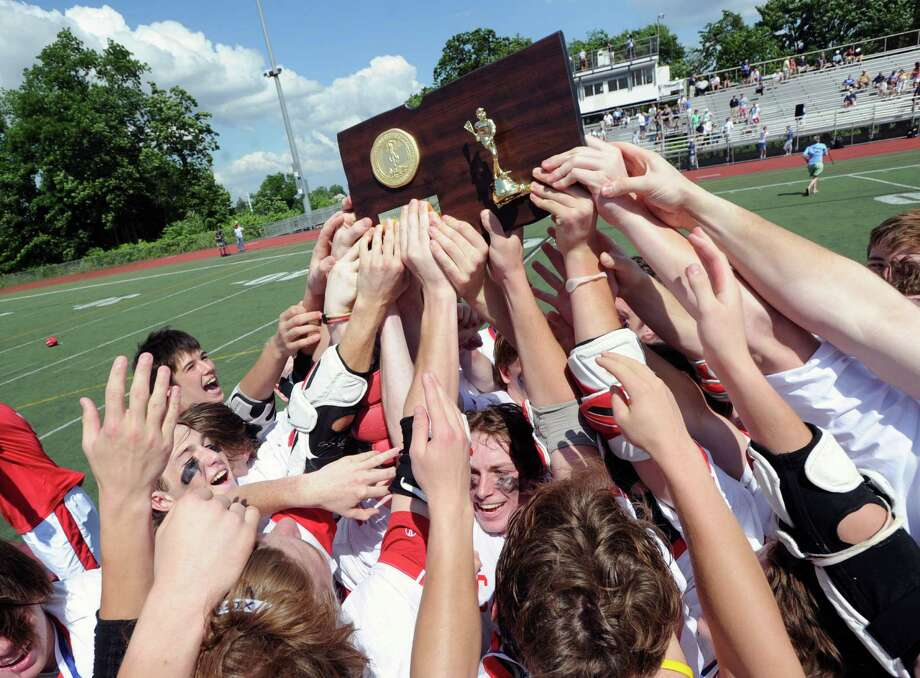 The Greenwich High School boys lacrosse team raises the Class L State Championship trophy above their heads at the conslusion of their match against Staples High School who they defeated 13-10 at Brien McMahon High School in Norwalk, Saturday, June 14, 2014. Photo: Bob Luckey / Greenwich Time