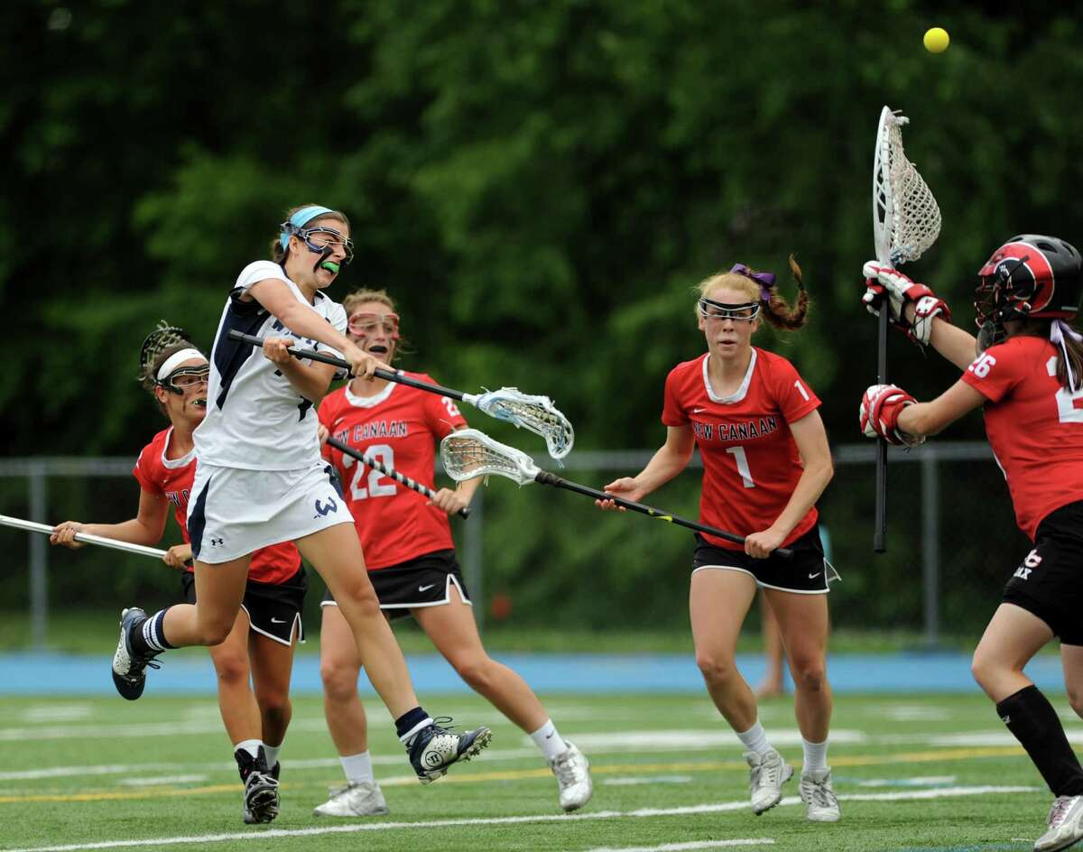 Wilton's Annie Cornbrooks slings the ball past New Canaan goalie Bailey Pilder Saturday, June 14, 2014, during the Class M Girls Lacrosse final at Bunnell High School in Stratford, Conn.