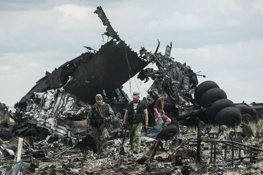 Pro-Russian fighters collect ammunition from the site where a Ukrainian army aircraft was downed near Luhansk, Ukraine. Photo: Evgeniy Maloletka, Associated Press