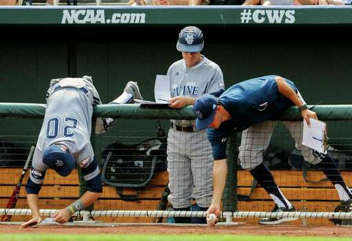 Eric Deragisch, UC Irvine baseball director of operations, right, and infielder John Brontsema (20), lean over the fence to snag a foul ball hit in the fourth inning of an NCAA baseball College World Series game against Texas in Omaha, Neb., Saturday, June 14, 2014. (AP Photo/Dave Weaver) Photo: Dave Weaver, Associated Press / FR67562 AP