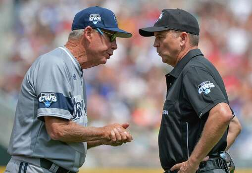 UC Irvine coach Mike Gillespie, left, has words with first base umpire Doug Williams after UC Irvine's Connor Spencer grounded out to Texas' shortstop C.J Hinojosa, in the third inning of an NCAA baseball College World Series game in Omaha, Neb., Saturday, June 14, 2014. (AP Photo/Ted Kirk) Photo: Ted Kirk, Associated Press / FR34398 AP