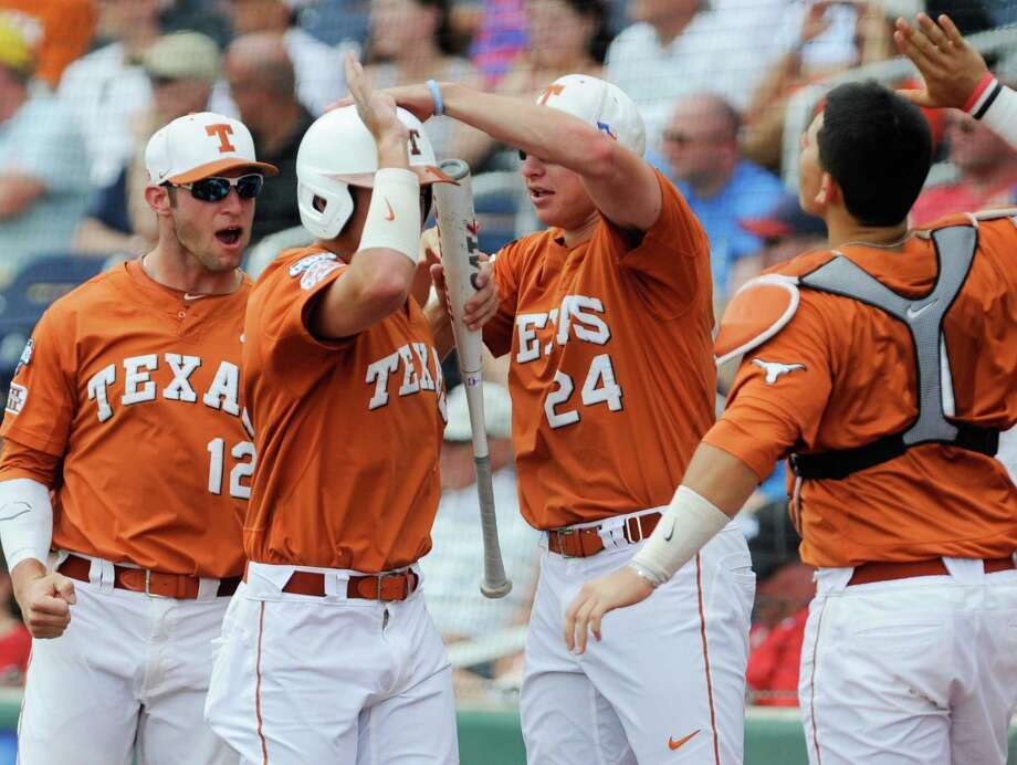 Texas players including Parker French (24) and Jacob Felts (12) greet Collin Shaw, center, to the dugout after he scored against UC Irvine in the second inning of an NCAA baseball College World Series game on a bunt by teammate Zane Gurwitz, in Omaha, Neb., Saturday, June 14, 2014. . (AP Photo/Dave Weaver) Photo: Dave Weaver, Associated Press / FR67562 AP