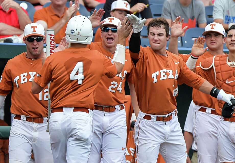Texas players including Parker French (24) greet Collin Shaw (4) to the dugout after he scored against UC Irvine in the second inning of an NCAA baseball College World Series game on a bunt by teammate Zane Gurwitz, in Omaha, Neb., Saturday, June 14, 2014. (AP Photo/Ted Kirk) Photo: Ted Kirk, Associated Press / FR34398 AP