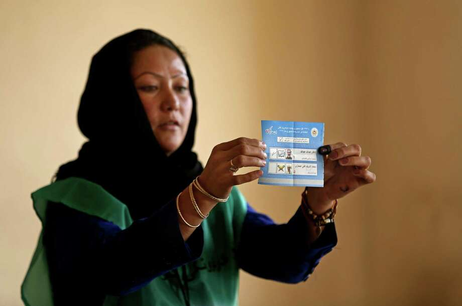 An Independent Election Commission (IEC) employee shows a ballot to observers at a polling station in Kabul, Afghanistan, Saturday, June 14, 2014. Despite a Taliban threat to stay away, Afghans lined up Saturday to vote in a presidential runoff between two candidates who both promise to improve ties with the West and combat corruption as they confront a powerful Taliban insurgency and preside over the withdrawal of most foreign troops by the end of the year. (AP Photo/Massoud Hossaini) Photo: Massoud Hossaini, STF / AP
