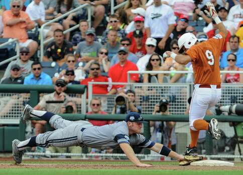 UC Irvine first baseman Connor Spencer, left, leaps late to first base as Texas' C.J Hinojosa (9) is safe following a throwing error by UC Irvine third baseman Taylor Sparks, during the fifth inning of an NCAA College World Series baseball game in Omaha, Neb., Saturday, June 14, 2014. (AP Photo/Dave Weaver) Photo: Dave Weaver, Associated Press / FR67562 AP