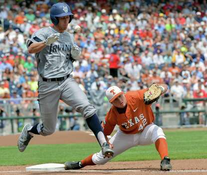 UC Irvine's Taylor Sparks (25) reaches first base on a throwing error by second baseman Brooks Marlow, unseen, as Texas first baseman Kacy Clemens (42) can't catch the ball, in the first inning of an NCAA baseball College World Series game in Omaha, Neb., Saturday, June 14, 2014. (AP Photo/Ted Kirk) Photo: Ted Kirk, Associated Press / FR34398 AP
