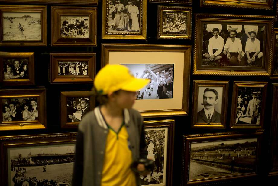 A young Brazilian fan looks at old photographs at the Hall of Origins in the Soccer Museum a few hours before the start of the World Cup inauguration match in Sao Paulo, Brazil, Thursday, June 12, 2014.  The museum dedicates ample space to explain the importance of Charles Miller, an English-educated Brazilian who brought soccer to Brazil from England, and is celebrated in Brazil as the forefather of Brazilian soccer. (AP Photo/Dario Lopez-Mills) Photo: Dario Lopez-Mills, Associated Press